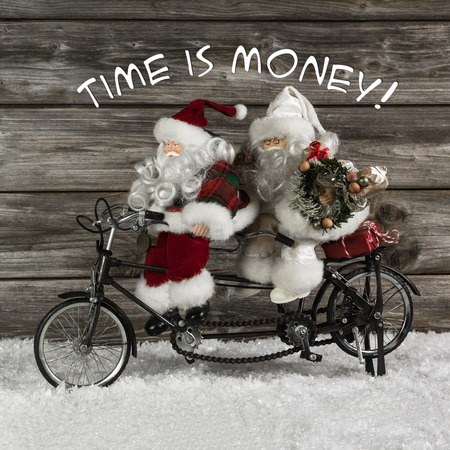 humorously: Time is money -  santa claus team in rush for buying christmas presents  Funny photo in vintage style with an old tandem bike of tin