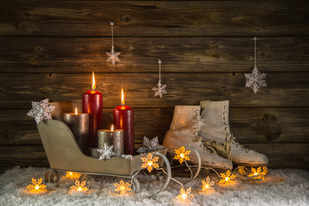 Christmas decoration in country style with four red burning candles and old skates in the wooden rustic background. photo