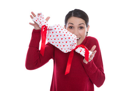 humorously: Isolated happy smiling young woman holding a present with red hearts in her hands. Stock Photo