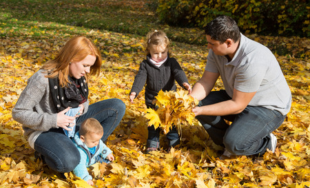 Happy young family in fall making a walk and play with maple leaves. photo