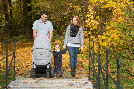 Happy young family in autumn making together a walk in the nature. photo