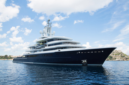 Gigantic big and large luxury mega yacht with helicopter landing place on the blue ocean. Investment for millionaires.