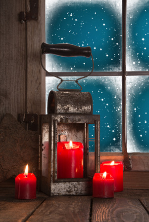 Traditional christmas decoration in red: four burning candles decorated on the window with an old tin lantern. photo