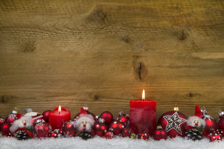 Merry christmas: Classic christmas decoration in red and white with two burning candles on wooden background. photo
