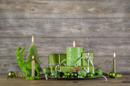 Christmas greeting card in green color. Decoration with candles and presents on wooden background.