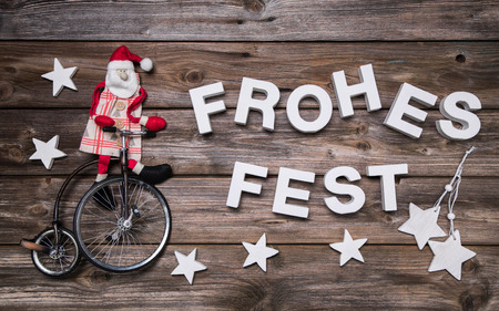 German christmas greeting card with german text. Xmas decoration with a red santa claus on a bicycle. photo