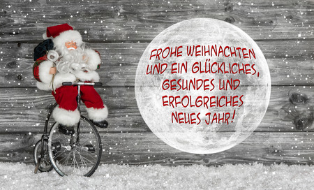 Merry christmas card in red and white with german text and a santa claus. photo