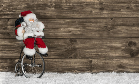 Wooden christmas background with santa on a bike.  photo