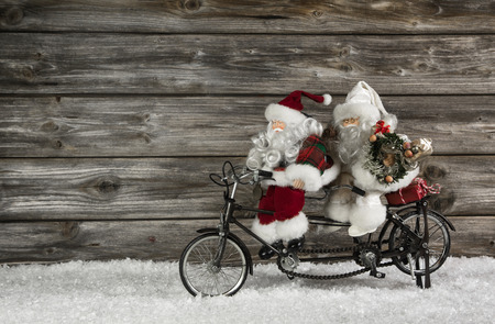 Funny wooden christmas background with two santa claus on a bicycle making xmas shopping. Also witty concept for teamwork. photo