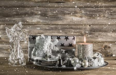 luz de velas: Plata y la decoración de navidad de color beige con el presente, ángel y la vela encendida en el fondo de madera. Foto de archivo