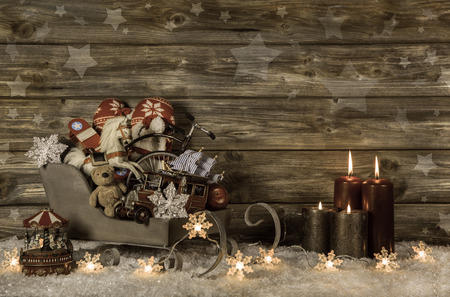 Old children toys and four red burning advent candles on wooden vintage background for decoration. photo
