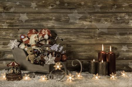 Oud kinderspeelgoed en vier rode brandende kaarsen op komst houten uitstekende achtergrond voor decoratie.