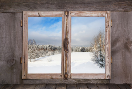 Snowy winter landscape in january. View out of an old rustic wooden window. Stock Photo
