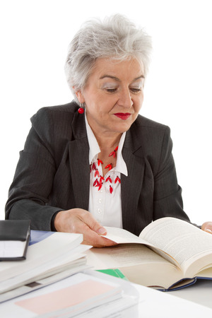 Older business woman sitting at desk reading in a book. Idea for a learning concept in the age. photo