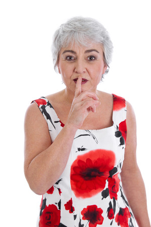 Isolated attractive mature woman making silence or attention gesture with her finger over white background. photo