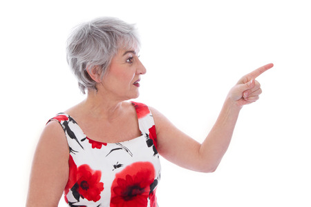 Attractive older woman isolated over white and wearing a red summer dress pointing with her finger. photo