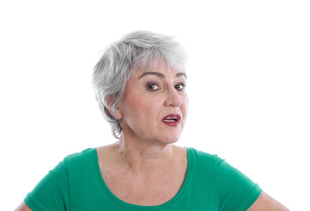 Isolated disappointed mature woman wearing green shirt looking angry and doubtful.