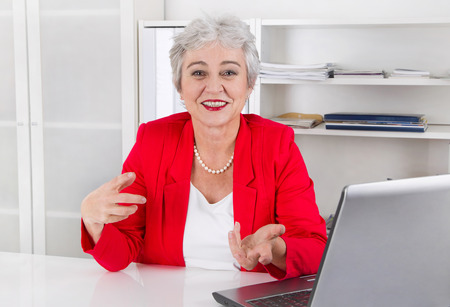 Attractive older smiling senior businesswoman sitting at desk wearing red jacket and explain something. photo