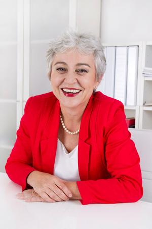 Attractive older senior businesswoman sitting at desk. photo