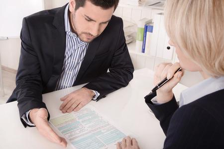 dialogo: Asesor sentado en una reuni�n con un espacio en blanco en la mesa de explicar algo a su colega. Foto de archivo