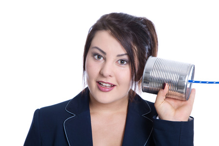 tin can phone: Stunned and nosy young businesswoman isolated over white holding a tin can for concepts in her hand.