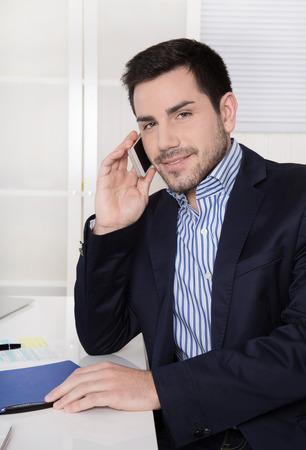 gigolo: Smart businessman sitting at desk talking on mobile.