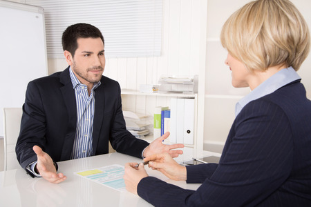 Job interview or meeting situation: business man and woman sitting at desk explaining something.