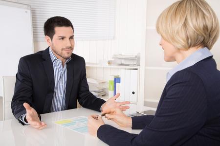 personas platicando: Entrevista de trabajo o situación reunión: hombre y mujer de negocios sentado en el escritorio explicando algo.