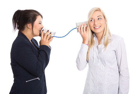 Woman talk: two isolated young woman talking with tin can. Concept for communication.