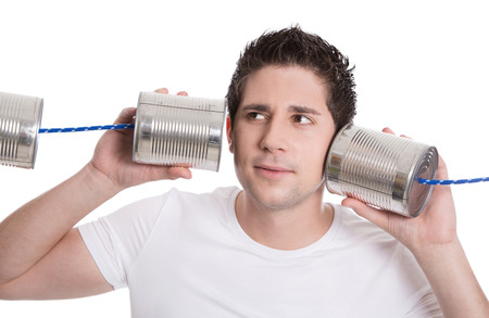 Isolated young man in white holding tin can. Communication or decision concepts.