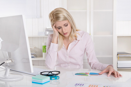 acoso laboral: Deprimido y frustrado joven empresaria sentado en el escritorio con dolor de cabeza.