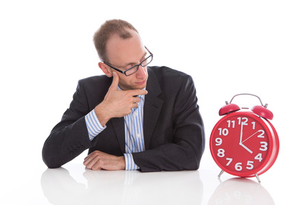 closing time: Closing time at four oclock: isolated businessman looking pensive an unhappy at a red alarm clock.