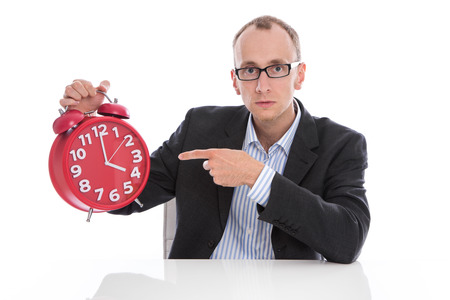 oclock: Stressed isolated businessman pointing at red alarm clock. 4 oclock afternoon.