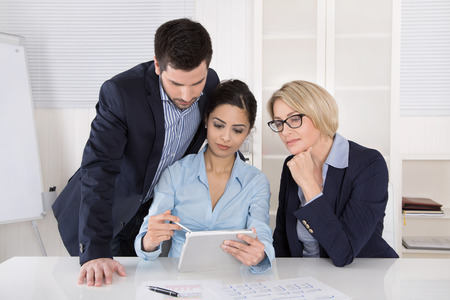 managing: Group of a professional business team sitting at the table talking together. Male and female people wearing blue clothes. Stock Photo