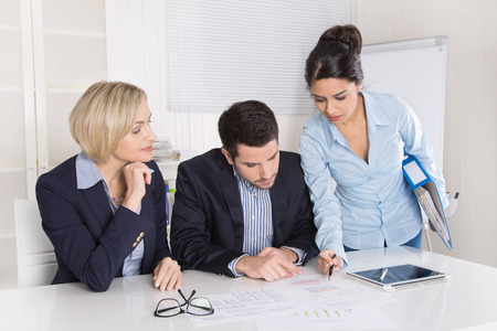 controlling: Group of a professional business team sitting at the table talking together. Male and female people wearing blue clothes. Stock Photo