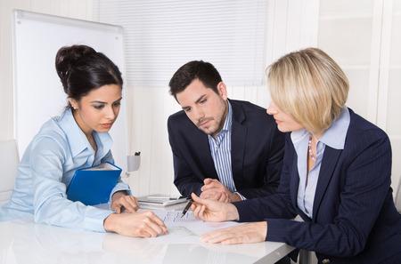 Groupe d'une équipe professionnelle d'affaires assis à la table à parler ensemble. Gens, hommes et femmes portant des vêtements bleus. Banque d'images