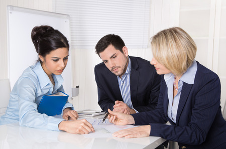 Group of a professional business team sitting at the table talking together. Male and female people wearing blue clothes. Archivio Fotografico