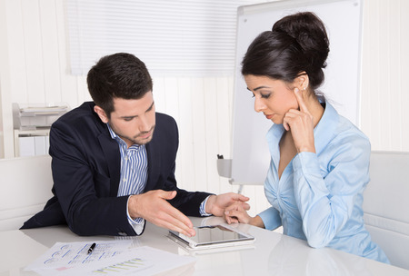 outgoings: Business meeting: professional successful team; man and woman talking together looking at tablet pc.