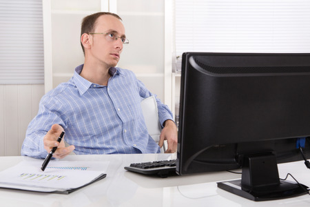 burn out: Listless and overworked business man sitting at desk with computer. Stock Photo