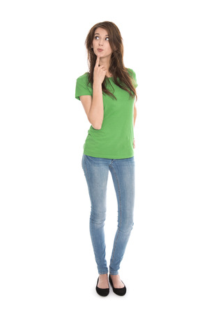 amused: Slim young woman wearing green shirt and blue jeans in full body length looking pensive and amused up to the text.