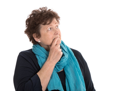 sorrowful: Isolated stunned senior woman in blue looking pensive and sorrowful sideways.