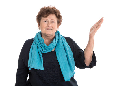 humorously: Pretty happy older isolated woman in blue presenting over white with hand.