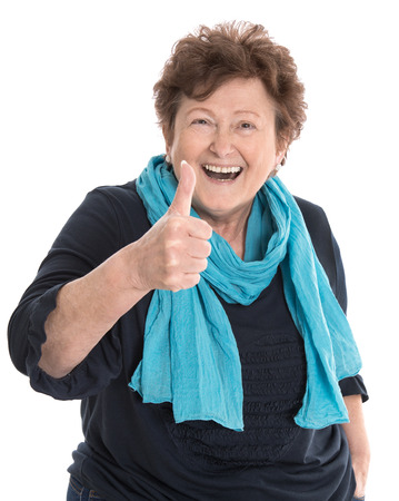 humorously: Happy isolated older lady wearing blue clothes with thumb up gesture over white background. Stock Photo