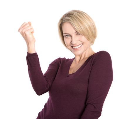 Geïsoleerde succesvol en gelukkig oudere vrouw in trui maken vuist gebaar