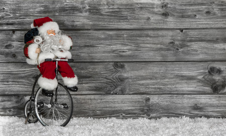 Funny Santa buying christmas presents decorated on wooden grey background  Stock Photo