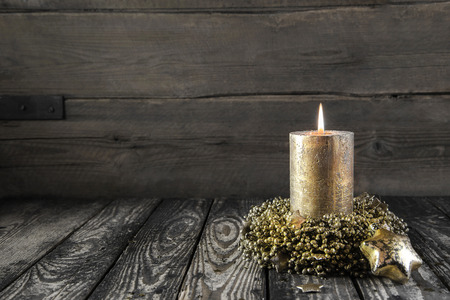 advent candles: One golden burning advent candle on wooden nostalgic background  Stock Photo