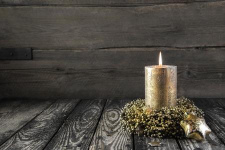 velas de navidad: Una de oro advenimiento quema en el fondo nostálgico de madera Foto de archivo