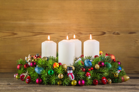 Colorful advent wreath with four white burning candles on wooden background. photo