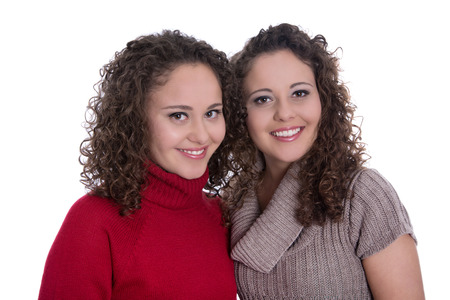 Siblings: two monozygotic young twin womans in portrait isolated over white background wearing winter pullovers. photo
