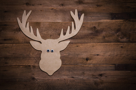 humorously: Wooden christmas background with antlers or reindeer hunting decoration.